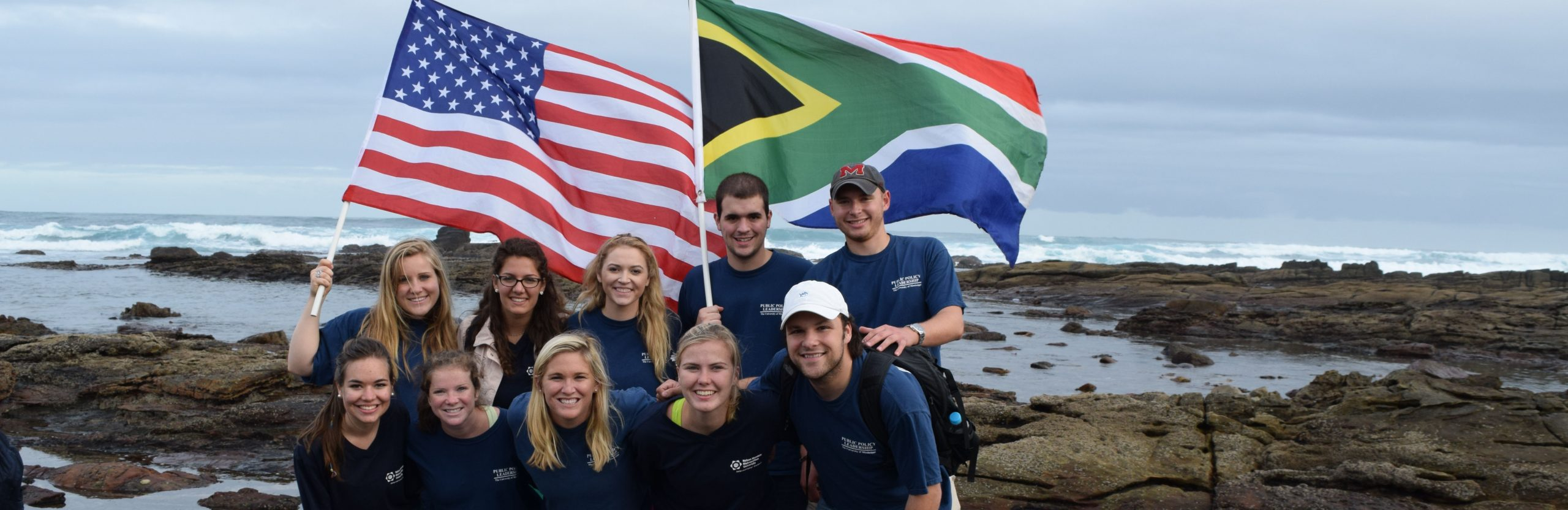 Students hold American and South African flags while studying abroad in South Africa